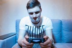 Junger Mann examininng seine Konsole zu Hause Stockfoto