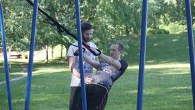 Junger Mann fängt an, ZugUPS auf Eignungsschleifen unter Steuerung des bärtigen Eignungstrainers im Sommerpark zu tun 4K langsame stock video footage
