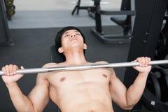 junger Mann führen Übung mit Gewichthebenmaschine in der Eignungsmitte durch männlicher Athlet pumpen oben Muskel in der Turnhall Stockfoto