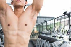 junger Mann führen Übung mit Maschine in der Eignungsmitte durch männliches Athletentraining in der Turnhalle sportlicher Kerl, d Lizenzfreies Stockfoto