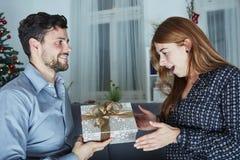 Junger Mann geben ihrer Freundin einen Präsentkarton Stockfotografie