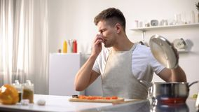 Junger Mann geekelt mit stinky Mahlzeit auf Ofen, verdorbene Bestandteile, untasty Nahrung stockfotos