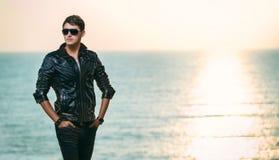 Junger Mann gegen das Meer bei Sonnenuntergang Lizenzfreies Stockfoto
