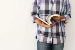 Junger Mann gegen die Wand ein Buch lesend Stockfotos