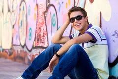 Junger Mann gegen Graffitiwand Stockfoto