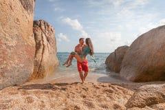 Junger Mann geht auf einen felsigen Strand mit einem Mädchen in seinen Armen Stockbilder