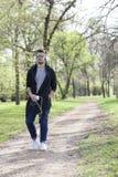 Junger Mann geht in den Park und hält das Telefon in seiner Hand und in L Stockfotografie