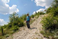 Junger Mann geht hinunter einen Hügel auf einer Steinstraße Stockfotografie