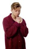 Junger Mann gekleidet in einer kastanienbraunen Strickjacke Stockfoto