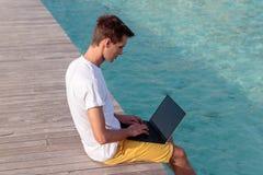 Junger Mann gesetzt auf einem Pier und dem Arbeiten mit seinem Laptop Klares blaues tropisches Wasser als Hintergrund lizenzfreie stockbilder