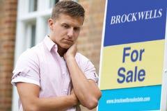 Junger Mann gezwungen, durch die Finanzprobleme, die draußen nahe bei für Verkaufs-Zeichen nach Hause zu verkaufen stehen lizenzfreie stockfotografie