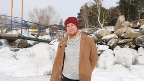 Junger Mann gibt ein Geschenk auf dem Hintergrund des Schnees und des Eises stockbild