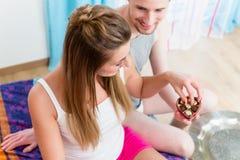Junger Mann gibt seine Freundinpraline für Valentinsgrüße DA Stockfotografie