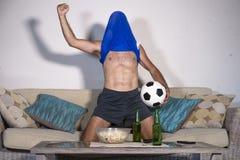 Junger Mann glücklich und aufgeregtes aufpassendes Fußballspiel im Fernsehen, welches das Siegziel verrückt mit Teamtrikot über s lizenzfreies stockfoto