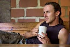 Junger Mann hält eine Kaffeetasse Stockbild