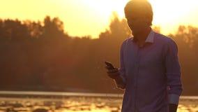 Junger Mann hört auf sein Mobile und tanzt an einem See stock footage