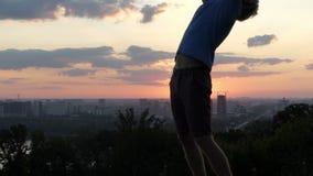 Junger Mann hebt Hände an und überspannt seins zurück bei Sonnenuntergang in SlomO stock video footage
