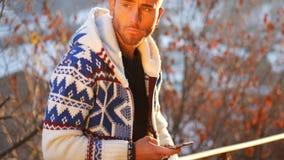 Junger Mann herein am Berg unter Verwendung des Handys Stockfotos