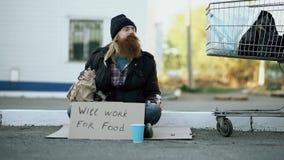 Junger Mann hilft zum Obdachloser und zum Geben ihm etwas Geldes während Bettlergetränkalkohol und sitzt nahe Warenkorb an stock footage