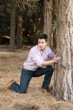 Junger Mann hinter einem Baum Stockfotografie