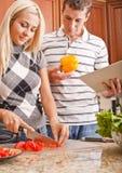 Junger Mann-Holding-Buch nahe bei dem Frauen-Kochen lizenzfreie stockbilder