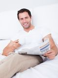 Junger Mann-Holding-Cup in der Hand, das Zeitung liest Lizenzfreies Stockbild