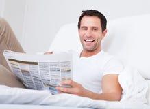 Junger Mann-Holding-Cup in der Hand, das Zeitung liest Stockbilder