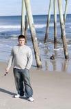Junger Mann-Holding-Sonnenbrillen am Strand Stockfotografie