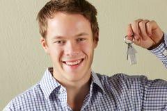 Junger Mann-Holding-Tasten zu erstem Haupt Stockfotos