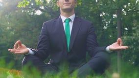 Junger Mann im Anzug, der in Lotussitz auf Gras, Freiheit des Verstandes sitzt stock video footage