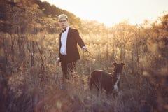 Junger Mann im Anzug und Bindung mit einem Windhundhund im aut Stockfotografie