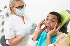 Junger Mann im Büro des Zahnarztes Stockbild