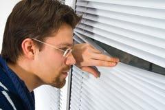 Junger Mann im Bademantel, der aus dem Fenster heraus schaut Lizenzfreie Stockfotos