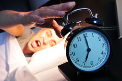 Junger Mann im Bett, das den Wecker stoppt Stockbilder