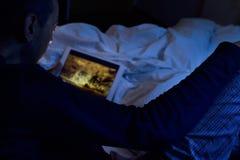 Junger Mann im Bett einen Film oder eine Reihe in seiner Tablette aufpassend Stockfotografie