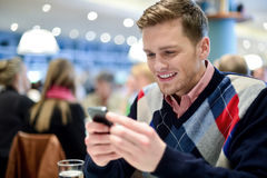 Junger Mann im Café und in der Anwendung seines Handys Lizenzfreie Stockfotografie