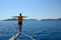 Junger Mann im gelben T-Shirt und rote kurze Hosen auf dem Bogen der Yacht streckten Arme wie Vogelflügel an einem sonnigen Tag d stockfotos