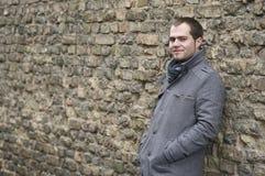 Junger Mann im grauen Mantel-Lächeln Stockfotos