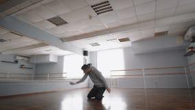 Junger Mann im grauen Pullover, der modernen Tanz im Ballsaal mit Barre herum tanzt Junger Fließenmann stellt dar stock video footage