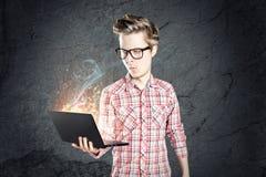 Junger Mann im Hemd und in der Fliege etwas auf Computer schreibend und Kamera mit Lächeln betrachtend Lizenzfreie Stockfotografie
