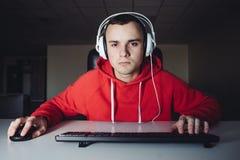 Junger Mann im Kopfhörer benutzt einen Computer Gamer spielt Spiele auf dem Computer Untersuchung die Kamera lizenzfreie stockfotos