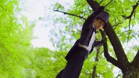 Junger Mann im Kostüm geht auf Stelzen im Park nahe Baum stock footage