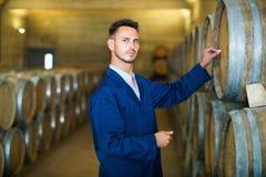Junger Mann im Mantel, der Kenntnisse über Weinfabrik nimmt lizenzfreies stockbild