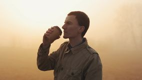 Junger Mann im Mantel seinen Morgenkaffee mit überraschender Ansicht während des Sonnenaufgangs trinkend stock video