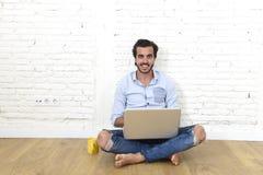 Junger Mann im modernen Blick der zufälligen Art des Hippies, der auf dem Wohnzimmerausgangsboden arbeitet an Laptop sitzt Stockbilder