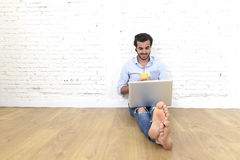 Junger Mann im modernen Blick der zufälligen Art des Hippies, der auf dem Wohnzimmerausgangsboden arbeitet an Laptop sitzt Lizenzfreie Stockbilder