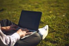 Junger Mann im Park, der auf dem Gras mit einem Laptop sitzt Mann Anwendungsund Schreibenlaptop-Computer im Sommergras stockfotografie