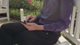 Junger Mann im Park unter Verwendung eines Telefons Stockbild