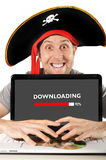 Junger Mann im Piratenkostüm mit Computerlaptopdownloading archiviert Copyrightverletzung Lizenzfreie Stockfotos