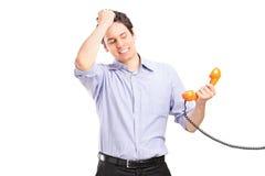 Junger Mann im Problem, das ein Telefonrohr hält Stockbild